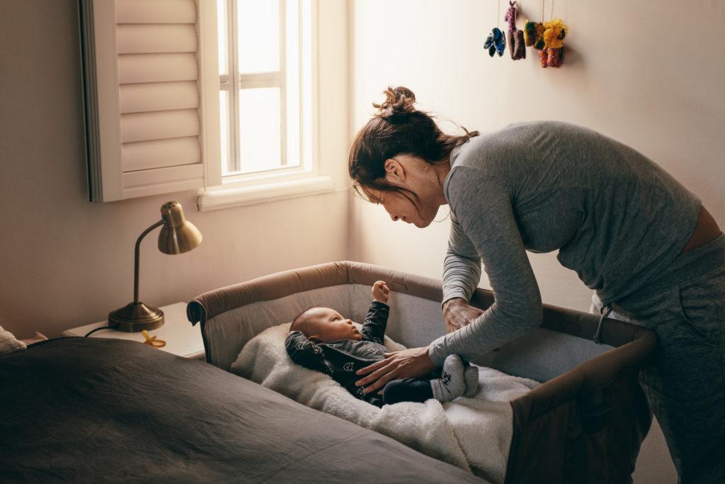 matka pochyla się nad łóżeczkiem dziecka