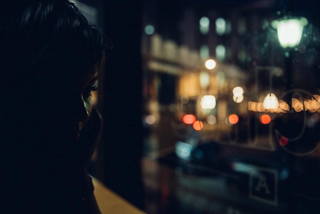 kobieta w ciemności patrzy w szybę